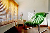 Green lounger and side table in front of large window with venetian blind