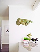 Hand sculpture with an extended index finger on a white wall above the kitchen counter