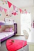 Happy children's room with pennants and lots of color accents in purple and pink