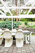 Terrace table with panton chairs under a bare, white pergola