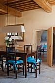 Wuchtige Holzbalkendecke in altem, provenzalischem Landhaus; rustikaler Essplatz mit türkisblauen Sitzkissen