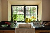 Kitchen counter with black worksurface and large stone sink below window with original glazing