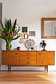Letter-shaped ornaments, bouquet and fan on 50s retro sideboard