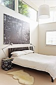 Black and white poster of city above French bed in bedroom with transom windows