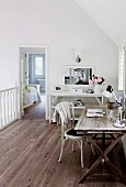 Home office on gallery with white shelves and wooden floor
