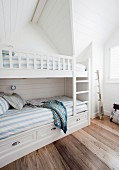 Bedroom with white bunk beds and blue and white striped bed linen in attic room with dark wooden floor