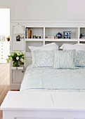 White, fitted shelving integrated in headboard of double bed