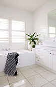 White washstand and bathtub in corner of bathroom below window with interior shutters of white slats