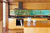 Island counter in front of kitchen counter with solid wood base units in residential house