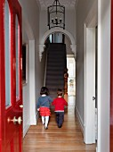 View through red-painted front door - two children walking along narrow hallway towards staircase