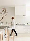 Woman walking in front of purist, white kitchen counter; bar stools at island block