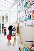 Little girl drawing on easel and collection of child's drawings pinned on wall in white interior with glass ceiling