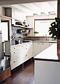 White fitted kitchen with dark wooden floor