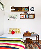 Bed with striped bedspread below floating shelves in child's bedroom