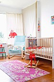 Bright nursery with cot, pale blue cantilever chair and red rocking moose