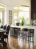 Stools at breakfast bar and rustic dining table with black upholstered chairs