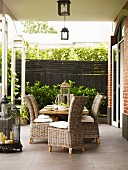 Wooden table and wicker chairs on terrace with antiquated decorative elements