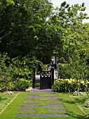 Front garden path of stone flags interspersed with lawn and Victorian-style front gate