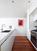 Flucht einer offenen Designerküche mit weissen Holchglanzfronten, Parkettboden & Wandbild