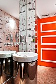 Marble sink with chrome base against mirrored wall with swan-shaped tap fitting; bright orange door with white mouldings in background