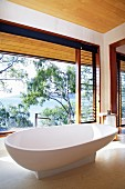 White, designer bathtub on stone floor in front of glass wall with view of sea and trees