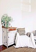 Simple, vintage-style, wooden cabinet next to armchair with white throw against white wall