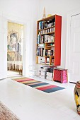 Red bookcase in white-painted room next to thread curtain in doorway