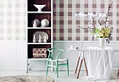Checkered wallpaper in natural colors; in front of it a white crockery shelf with a brown inner surface and a white table with an elegant bouquet of spring flowers