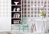 Karierte Wandtapete in Naturfarben; davor ein weisses Geschirrregal mit brauner Innenfläche und ein weisser Tisch mit elegantem Frühlingsblumenstrauss