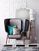 Modern, gray armchair standing in front of white, baroque mirror on white wooden pallets
