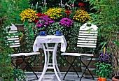 weiße Stühle und Tisch vor Blumenkasten auf einem Balkon