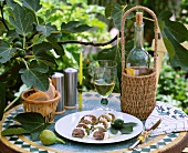 Plate of figs and ricotta and white wine on garden table