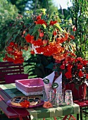 Fruit tart and glasses on garden table with red and orange trailing begonias