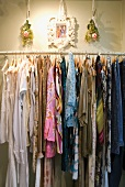 Women's clothing on hangers on wall-mounted clothes rail