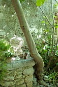 Overgrown charm - tealight holders on half-height stone wall and chandelier with bird hanging from tree