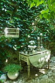 Vintage candlesticks on rustic wooden table against climber-covered facade (Virginia creeper)