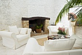 Elegant sofa set with pale upholstery in front of open fireplace on Mediterranean loggia