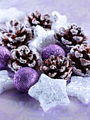 Christmas arrangement of purple baubles, stars and pine cones