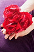 Rose petals arranged in the shape of a heart held in a woman's hands