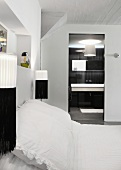 Black and white wall-mounted lamps either side of double bed with white bed linen and view into ensuite bathroom
