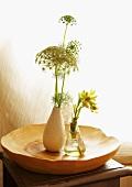 Zwei kleine Vasen mit Wiesenpflanzen in massiver, künstlerisch bearbeiteter Holzschale