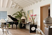 Music room with open, black grand piano; three vases of pink flowers on black sideboard against wall