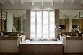 Marble bathtub below half-closed window shutters in spacious bathroom