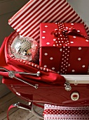 Christmas gifts and decorative bauble in red pram