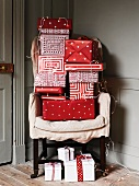 Gifts wrapped in red and white paper on armchair
