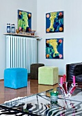 Glass coffee table on zebra skin rug, brightly coloured cubic stools in front of radiator and series of three pop art-style pictures of cows' heads