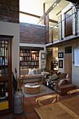 Mit recycelten Materialien gestalteter, hoher Wohnraum mit Galerie; Sofa mit Tierfellbezug, alte Milchkanne und Bibliothek im Hintergrund