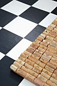 Mat hand-crafted from corks on black and white chequered floor tiles