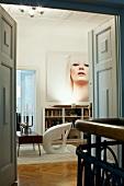 Blick durch offene Flügeltür auf weissen Designerstuhl vor Retro Couchtisch und grosses Frauenportrait an Wand in klassischem Ambiente