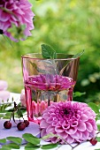 Pink dahlia in water glass decorating table